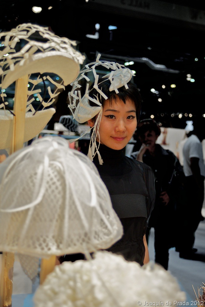 Honoyo Imai in front of her hats